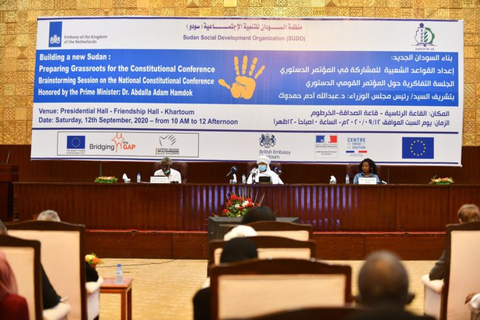 The Prime Minister of Sudan at the SUDO meeting. In the background, a banner with the name of the meeting and the logos of the sponsors