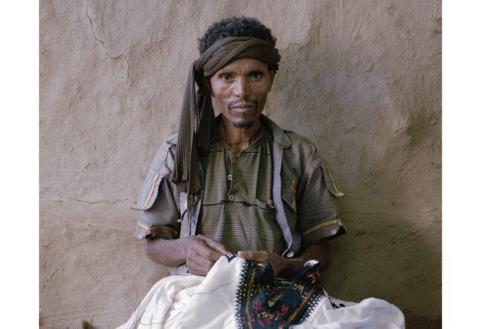 Ethiopian man sewing a traditional costume