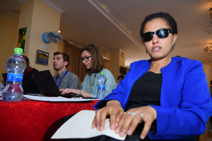 Ethiopian woman reads braille version of Briding the Gap's leaflet at the project launch event