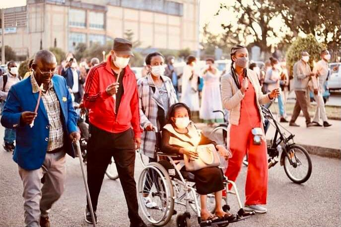 candlelight walk in the street involving persons with disabilities